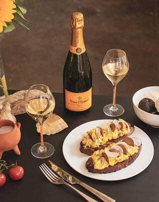 Fluffy scrambled eggs with summer truffles and radishes on grilled sourdough